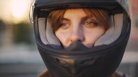Porträt des schönen jungen rothaarigen Frauenmotorradfahrers im Sturzhelm bei Sonnenuntergang stock footage