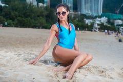 Porträt des schönen jungen weiblichen Modells in der Badebekleidung, die auf dem Strand am tropischen Erholungsort sitzt Stockfoto