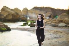 Porträt des schönen jungen weiblichen touristischen Fotografen mit Kamera in Meer Lizenzfreie Stockbilder