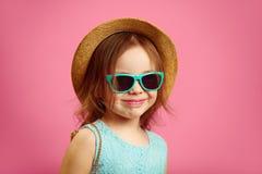 Portr?t des sch?nen kleinen M?dchens mit Strohhut und Sonnenbrille, tr?gt blaues Kleid, die St?nde auf rosa lokalisiert lizenzfreie stockfotografie