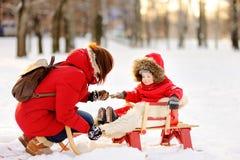 Porträt des schönen Kleinkindjungen und seiner der Mutter, die Spaß im schneebedeckten Park hat Stockbilder