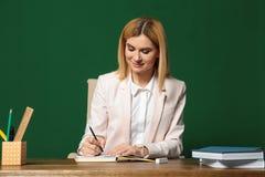 Porträt des schönen Lehrers bei Tisch sitzend lizenzfreie stockfotos