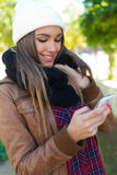 Porträt des schönen Mädchens, das ihren Handy in der Stadt verwendet Stockfotos