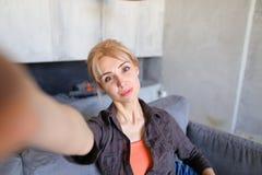 Porträt des schönen Mädchens, das Kamera auf länglicher Hand hält Lizenzfreie Stockfotografie