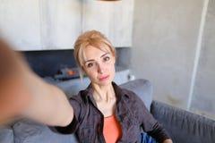 Porträt des schönen Mädchens, das Kamera auf länglicher Hand hält Stockbilder