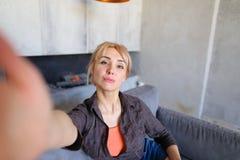 Porträt des schönen Mädchens, das Kamera auf länglicher Hand hält Lizenzfreie Stockfotos