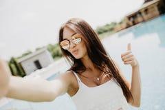 Porträt des schönen Mädchens ein selfie am Swimmingpool mit den Daumen oben nehmend Lizenzfreie Stockfotos