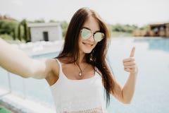 Porträt des schönen Mädchens ein selfie am Swimmingpool mit den Daumen oben nehmend Stockbilder