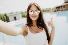Porträt des schönen Mädchens ein selfie am Swimmingpool mit den Daumen oben nehmend Lizenzfreie Stockbilder