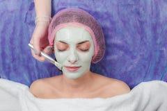 Porträt des schönen Mädchens Gesichtslehmmasken-Schönheitsbehandlungen anwendend Lizenzfreies Stockfoto
