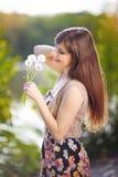 Porträt des schönen Mädchens im Park, der Löwenzahn hält Lizenzfreie Stockbilder