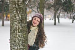 Porträt des schönen Mädchens im Schnee, der hinter einem Baum sich versteckt lizenzfreies stockfoto