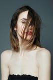 Porträt des schönen Mädchens im Studio mit rotem Lippenstift auf einem grauen Hintergrund Lizenzfreie Stockfotos