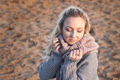 Porträt des schönen Mädchens lächelnd mit geschlossenen Augen und Schal auf Strand halten Lizenzfreies Stockbild