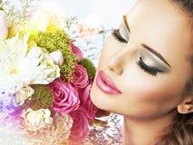 Porträt des schönen Mädchens mit Blumen in den Händen stockfotos