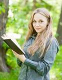 Porträt des schönen Mädchens mit Buch im Park Lizenzfreies Stockfoto