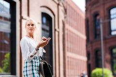 Porträt des schönen Mädchens mit einem Telefon in ihren Händen Lizenzfreies Stockfoto