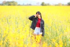 Porträt des schönen Mädchens mit gelben Blumen, sonniger Sommer stockfotografie