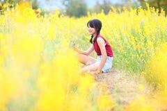 Porträt des schönen Mädchens mit gelben Blumen, sonniger Sommer lizenzfreie stockfotografie