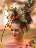Porträt des schönen Mädchens mit Herbstlaub und mit stilvollem m Lizenzfreie Stockfotos
