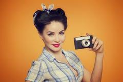 Porträt des schönen Mädchens mit Kamera auf gelb-orangeem backgroud Lizenzfreies Stockbild