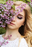 Porträt des schönen Mädchens mit lila Blumen Stockfotografie