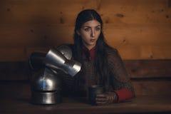 Porträt des schönen mittelalterlichen Mädchenkriegers in einer chainmail Haube mit Sturzhelm in den Händen stockfotos