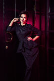 Porträt des schönen Mode-Modells im klassischen schwarzen Kleid, im Make-up und in der Frisur nahe dunkler Türstellung und -aufst stockfotografie
