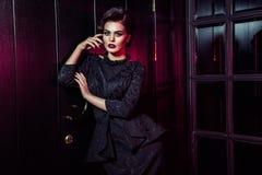 Porträt des schönen Mode-Modells im klassischen schwarzen Kleid, im Make-up und in der Frisur nahe dunkler Türstellung und -aufst lizenzfreies stockbild