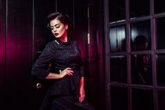 Porträt des schönen Mode-Modells im klassischen schwarzen Kleid, im Make-up und in der Frisur nahe dunkler Türstellung und -aufst stockbild