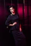 Porträt des schönen Mode-Modells im klassischen schwarzen Kleid, im Make-up und in der Frisur nahe dunkler Türstellung und -aufst lizenzfreies stockfoto