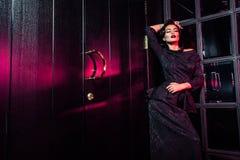 Porträt des schönen Mode-Modells im klassischen schwarzen Kleid, im Make-up und in der Frisur nahe dunkler Türstellung und -aufst lizenzfreie stockfotos