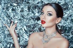 Porträt des schönen Modells mit Feiertagsmake-up, den roten Lippen und glänzendem Diamantschmuck auf Funkelnhintergrund Stockfoto