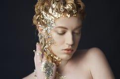 Porträt des schönen Modells mit glänzender Folie auf Gesicht und Haar Stockfotografie