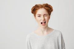 Porträt des schönen Rothaarigemädchens, das die Zunge zeigend blinzelt lächelt, Kamera über weißem Hintergrund betrachtend Stockfotos
