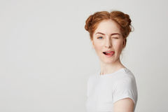 Porträt des schönen Rothaarigemädchens, das die Zunge zeigend blinzelt lächelt, Kamera über weißem Hintergrund betrachtend Stockbild