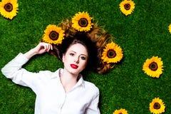 Porträt des schönen rothaarigen Mädchens mit Sonnenblumen lizenzfreie stockbilder
