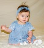 Porträt des schönen süßen kleinen Babys in einem blauen Kleid mit einer Haarnadel auf dem Kopf, der lächelt Stockbild