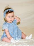 Porträt des schönen süßen kleinen Babys in einem blauen Kleid mit einer Haarnadel auf dem Kopf, der lächelt Lizenzfreies Stockfoto