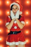 Porträt des schönen sexy Mädchens, das Santa Claus trägt, kleidet auf rotem Hintergrund stockfoto