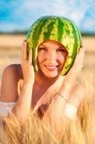 Porträt des schönen sexy Modells der jungen Frau mit Wassermelone auf Kopf Stockfotografie