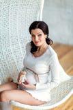 Porträt des schönen sexy schwangeren Brunette in einem weißen Studio w Stockfotos