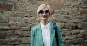 Porträt des schönen stilvollen Mädchens in der Sonnenbrille, die draußen lächelnd steht stock footage