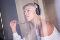Porträt des schönen traurigen Mädchens mit Kopfhörern hörend Rockmusik Lizenzfreie Stockfotografie