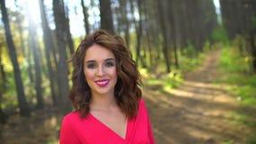 Porträt des Schönheits-Mädchens im roten Kleid mit dem gesunden langen Haar in der Waldglücklichen Frau, die herein im Herbst smi stock video