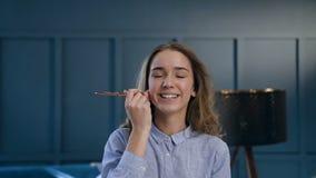 Porträt des Schönheitsfrauenwählens bilden Bürste und zutreffend erröten Sie auf den Wangenknochen unter Verwendung der großen Bü stock footage