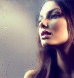 Porträt des Schönheitsmädchens hinter dem nassen Glas Stockfoto