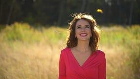 Porträt des Schönheitsmädchens im roten Kleid mit dem gesunden langen Haar im Waldgesicht der glücklichen Frau im Herbst im sonni stock footage
