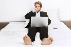 Porträt des schläfrigen attraktiven reifen Unternehmensdirektors, der im Bett, schließend Mund mit der Hand mit der Hand beim Gäh Stockbilder