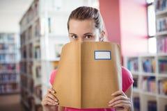 Porträt des Schulmädchens ihr Gesicht mit Buch in der Bibliothek versteckend Stockbild